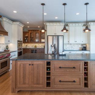 Geräumige Urige Küche in U-Form mit Landhausspüle, Schrankfronten im Shaker-Stil, weißen Schränken, Küchenrückwand in Grau, Küchengeräten aus Edelstahl, braunem Holzboden, Kücheninsel, braunem Boden und grauer Arbeitsplatte in Sonstige