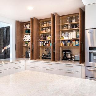 Klassisk inredning av ett stort kök, med släta luckor, skåp i mellenmörkt trä, bänkskiva i kvartsit, vitt stänkskydd, stänkskydd i keramik, rostfria vitvaror och en köksö