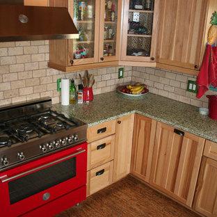 На фото: угловая кухня среднего размера с накладной раковиной, стеклянными фасадами, светлыми деревянными фасадами, столешницей из переработанного стекла, бежевым фартуком, фартуком из известняка, цветной техникой и темным паркетным полом с