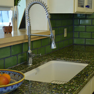 Mid-sized southwestern kitchen appliance - Kitchen - mid-sized southwestern galley kitchen idea in Phoenix with an undermount sink, glass-front cabinets, yellow cabinets, recycled glass countertops, green backsplash, ceramic backsplash and white appliances