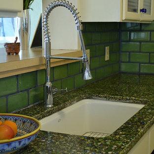 フェニックスの中サイズのサンタフェスタイルのおしゃれなII型キッチン (アンダーカウンターシンク、ガラス扉のキャビネット、黄色いキャビネット、再生ガラスカウンター、緑のキッチンパネル、セラミックタイルのキッチンパネル、白い調理設備) の写真