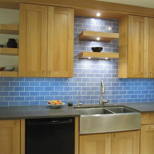 Photo of a mid-sized transitional kitchen in Phoenix with a farmhouse sink, shaker cabinets, light wood cabinets, recycled glass benchtops, blue splashback, subway tile splashback and black appliances.