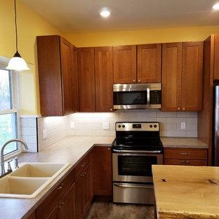 グランドラピッズの中くらいのトラディショナルスタイルのおしゃれなキッチン (ドロップインシンク、シェーカースタイル扉のキャビネット、中間色木目調キャビネット、シルバーの調理設備、白いキッチンパネル、セラミックタイルのキッチンパネル、木材カウンター、クッションフロア、グレーの床、ベージュのキッチンカウンター) の写真