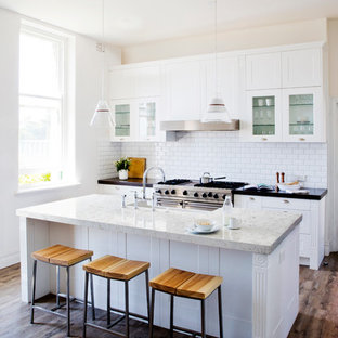 Design ideas for a small modern single-wall kitchen in Baltimore with a drop-in sink, flat-panel cabinets, white cabinets, quartzite benchtops, white splashback, glass tile splashback, stainless steel appliances, dark hardwood floors and with island.
