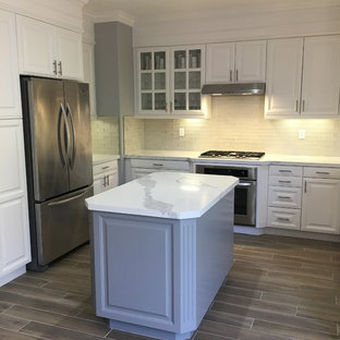 Photo of a mid-sized transitional u-shaped kitchen in San Francisco with an undermount sink, stainless steel appliances, porcelain floors, brown floor, raised-panel cabinets, white cabinets, quartzite benchtops, grey splashback, ceramic splashback, with island and turquoise benchtop.