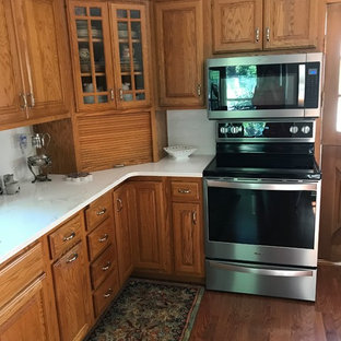 This is an example of a small traditional l-shaped separate kitchen in Cedar Rapids with an undermount sink, raised-panel cabinets, medium wood cabinets, quartz benchtops, white splashback, subway tile splashback, stainless steel appliances, carpet, no island, multi-coloured floor and white benchtop.