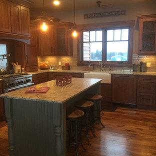 他の地域のシャビーシック調のおしゃれなキッチン (エプロンフロントシンク、御影石カウンター、シルバーの調理設備、シェーカースタイル扉のキャビネット、中間色木目調キャビネット、ベージュキッチンパネル、ボーダータイルのキッチンパネル、無垢フローリング) の写真