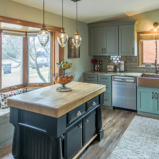 Design ideas for a small shabby-chic style l-shaped eat-in kitchen in Detroit with a farmhouse sink, shaker cabinets, green cabinets, quartz benchtops, grey splashback, glass tile splashback, stainless steel appliances, dark hardwood floors, with island, brown floor and beige benchtop.