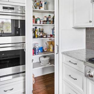 デトロイトの中くらいのトランジショナルスタイルのおしゃれなキッチン (アンダーカウンターシンク、シェーカースタイル扉のキャビネット、白いキャビネット、クオーツストーンカウンター、ベージュキッチンパネル、磁器タイルのキッチンパネル、シルバーの調理設備、無垢フローリング、茶色い床、ベージュのキッチンカウンター) の写真