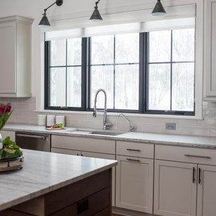 Inspiration för ett avskilt, mellanstort funkis l-kök, med en undermonterad diskho, skåp i shakerstil, vita skåp, vitt stänkskydd, rostfria vitvaror, mellanmörkt trägolv och en köksö