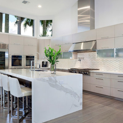 Example of a large trendy l-shaped medium tone wood floor eat-in kitchen design in Miami with an undermount sink, flat-panel cabinets, stainless steel appliances, an island, white cabinets, marble countertops, white backsplash and ceramic backsplash