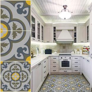 Foto de cocina mediterránea, sin isla, con armarios con paneles con relieve, salpicadero beige, salpicadero de piedra caliza, suelo de cemento y suelo amarillo