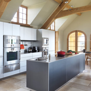 Photo of a country eat-in kitchen in London with an integrated sink, flat-panel cabinets, white cabinets, stainless steel benchtops, metallic splashback, stainless steel appliances, with island and beige floor.