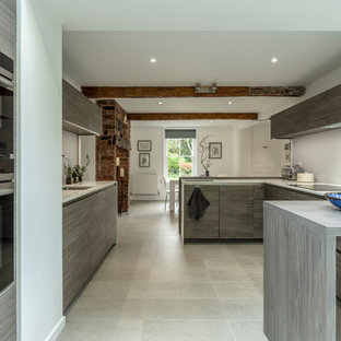 Design ideas for a contemporary u-shaped kitchen/diner in Cheshire with flat-panel cabinets, ceramic flooring, beige floors, a submerged sink, grey cabinets, grey splashback, integrated appliances, a breakfast bar and white worktops.