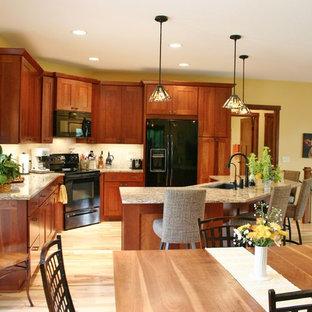 Foto på ett mellanstort amerikanskt kök, med en undermonterad diskho, skåp i shakerstil, skåp i mellenmörkt trä, bänkskiva i kvarts, beige stänkskydd, stänkskydd i stenkakel, svarta vitvaror, ljust trägolv och en köksö