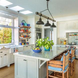 Bild på ett stort maritimt l-kök, med en rustik diskho, bänkskiva i kvartsit, vitt stänkskydd, stänkskydd i keramik, rostfria vitvaror, en köksö, brunt golv, luckor med infälld panel, beige skåp och mörkt trägolv