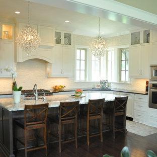 Große Klassische Wohnküche in L-Form mit Waschbecken, Schrankfronten im Shaker-Stil, weißen Schränken, Granit-Arbeitsplatte, Küchenrückwand in Weiß, Rückwand aus Steinfliesen, Küchengeräten aus Edelstahl, dunklem Holzboden und Kücheninsel in Austin