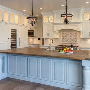 Immagine di una cucina classica con ante con bugna sagomata, ante beige, top in legno, paraspruzzi multicolore, elettrodomestici da incasso, parquet scuro, isola e pavimento marrone