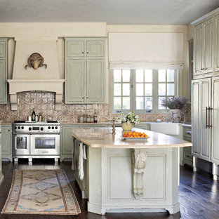 Inspiration for a shabby-chic style u-shaped dark wood floor and brown floor enclosed kitchen remodel in Houston with a farmhouse sink, raised-panel cabinets, distressed cabinets, brown backsplash, stainless steel appliances and an island