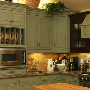 Inspiration for a large country l-shaped kitchen pantry in Orange County with a farmhouse sink, raised-panel cabinets, green cabinets, granite benchtops, orange splashback, subway tile splashback, stainless steel appliances, ceramic floors and with island.