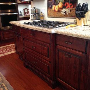 Große Klassische Wohnküche in U-Form mit Unterbauwaschbecken, profilierten Schrankfronten, beigen Schränken, Granit-Arbeitsplatte, bunter Rückwand, Rückwand aus Keramikfliesen, Küchengeräten aus Edelstahl, braunem Holzboden und Kücheninsel in Sacramento