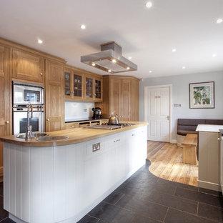 На фото: кухни в классическом стиле с техникой из нержавеющей стали, раковиной в стиле кантри, столешницей из гранита, фасадами с утопленной филенкой, светлыми деревянными фасадами и островом