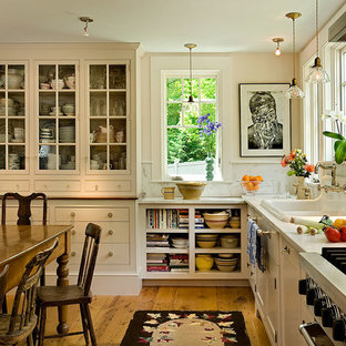 Photo of a traditional eat-in kitchen in Burlington with a drop-in sink, glass-front cabinets, beige cabinets, white splashback, stone slab splashback and stainless steel appliances.