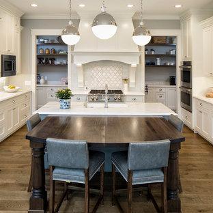 ミネアポリスの大きいトラディショナルスタイルのおしゃれなキッチン (エプロンフロントシンク、白いキャビネット、白いキッチンパネル、パネルと同色の調理設備、無垢フローリング、シェーカースタイル扉のキャビネット、大理石カウンター、サブウェイタイルのキッチンパネル) の写真