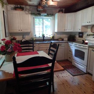 ボストンのラスティックスタイルのおしゃれなL型キッチン (アンダーカウンターシンク、レイズドパネル扉のキャビネット、ベージュのキャビネット、人工大理石カウンター、白い調理設備、淡色無垢フローリング) の写真