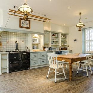 Design ideas for a rural kitchen/diner in Other with raised-panel cabinets, blue cabinets, white splashback, black appliances, dark hardwood flooring and metro tiled splashback.