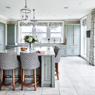 Classic kitchen in Cheshire with beaded cabinets, grey cabinets, grey splashback, black appliances, an island, beige floors and grey worktops.
