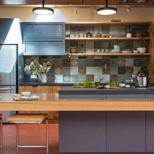 他の地域の巨大なインダストリアルスタイルのおしゃれなキッチン (ダブルシンク、フラットパネル扉のキャビネット、中間色木目調キャビネット、人工大理石カウンター、マルチカラーのキッチンパネル、セラミックタイルのキッチンパネル、シルバーの調理設備、リノリウムの床、赤い床、黒いキッチンカウンター) の写真