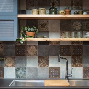 アデレードの巨大なインダストリアルスタイルのおしゃれなキッチン (ダブルシンク、フラットパネル扉のキャビネット、中間色木目調キャビネット、人工大理石カウンター、マルチカラーのキッチンパネル、セラミックタイルのキッチンパネル、シルバーの調理設備の、リノリウムの床、赤い床、黒いキッチンカウンター) の写真
