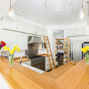 This is an example of a rural u-shaped open plan kitchen in Hampshire with a double-bowl sink, shaker cabinets, white cabinets, wood worktops, stainless steel appliances, medium hardwood flooring and a breakfast bar.