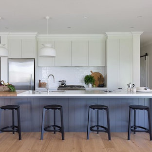 Design ideas for a large country galley eat-in kitchen in Wollongong with white cabinets, quartz benchtops, white splashback, ceramic splashback, stainless steel appliances, with island, white benchtop, an undermount sink, recessed-panel cabinets, medium hardwood floors and beige floor.
