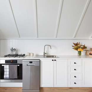 Design ideas for a mid-sized country l-shaped kitchen in Wollongong with white cabinets, quartz benchtops, white splashback, ceramic splashback, stainless steel appliances, white benchtop, a drop-in sink, shaker cabinets and no island.