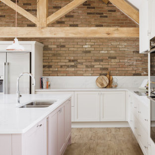 他の地域の中くらいのカントリー風おしゃれなキッチン (ダブルシンク、シェーカースタイル扉のキャビネット、ピンクのキャビネット、人工大理石カウンター、白いキッチンパネル、クオーツストーンのキッチンパネル、シルバーの調理設備、淡色無垢フローリング、茶色い床、白いキッチンカウンター、三角天井) の写真