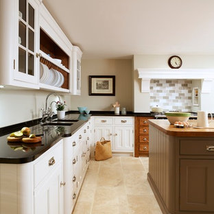Photo of a medium sized rural l-shaped enclosed kitchen in Essex with an island, flat-panel cabinets, white cabinets, granite worktops, a submerged sink, multi-coloured splashback, ceramic splashback and travertine flooring.
