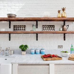 Diseño de cocina campestre con fregadero sobremueble, armarios abiertos y salpicadero blanco