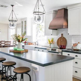 Landhaus Wohnküche in L-Form mit Landhausspüle, Schrankfronten im Shaker-Stil, weißen Schränken, Onyx-Arbeitsplatte, Küchenrückwand in Weiß, Rückwand aus Metrofliesen, schwarzen Elektrogeräten, braunem Holzboden, Kücheninsel und braunem Boden in Las Vegas