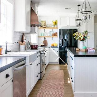 ラスベガスのカントリー風おしゃれなキッチン (エプロンフロントシンク、シェーカースタイル扉のキャビネット、白いキャビネット、オニキスカウンター、白いキッチンパネル、サブウェイタイルのキッチンパネル、黒い調理設備、無垢フローリング、茶色い床) の写真