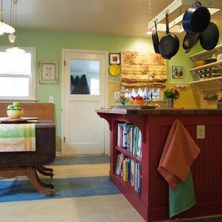 シアトルの中サイズのカントリー風おしゃれなキッチン (エプロンフロントシンク、フラットパネル扉のキャビネット、白いキャビネット、木材カウンター、ベージュキッチンパネル、木材のキッチンパネル、シルバーの調理設備の、クッションフロア、マルチカラーの床、茶色いキッチンカウンター) の写真
