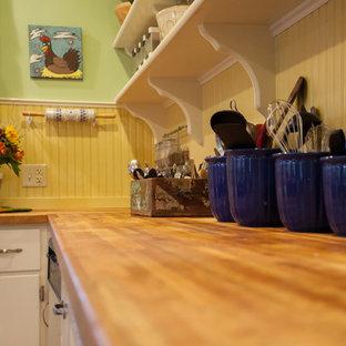 シアトルの中くらいのカントリー風おしゃれなキッチン (エプロンフロントシンク、フラットパネル扉のキャビネット、白いキャビネット、木材カウンター、ベージュキッチンパネル、木材のキッチンパネル、シルバーの調理設備、クッションフロア、マルチカラーの床、茶色いキッチンカウンター) の写真