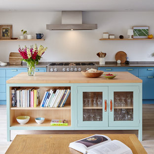 This is an example of a mid-sized country eat-in kitchen in Berkshire with an undermount sink, blue cabinets, limestone benchtops, stainless steel appliances, light hardwood floors, with island and flat-panel cabinets.