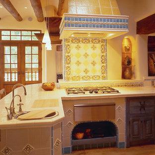 アルバカーキの中サイズの地中海スタイルのおしゃれなキッチン (ドロップインシンク、落し込みパネル扉のキャビネット、ヴィンテージ仕上げキャビネット、タイルカウンター、マルチカラーのキッチンパネル、セラミックタイルのキッチンパネル、シルバーの調理設備の、淡色無垢フローリング) の写真