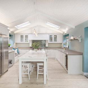 Medium sized farmhouse u-shaped kitchen/diner in London with a double-bowl sink, shaker cabinets, white cabinets, granite worktops, blue splashback, ceramic splashback, stainless steel appliances, light hardwood flooring and an island.