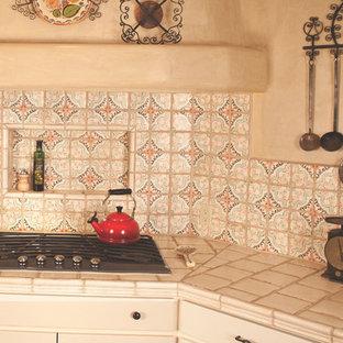 アルバカーキの中サイズの地中海スタイルのおしゃれなキッチン (エプロンフロントシンク、シェーカースタイル扉のキャビネット、ベージュのキャビネット、タイルカウンター、マルチカラーのキッチンパネル、テラコッタタイルのキッチンパネル、シルバーの調理設備の、テラコッタタイルの床) の写真