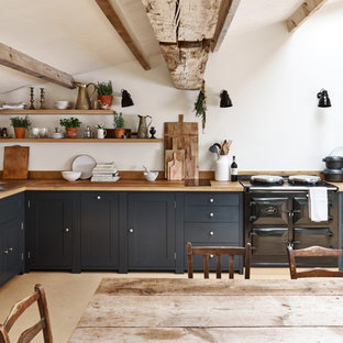 Inspiration for a medium sized country l-shaped kitchen/diner in Cheshire with recessed-panel cabinets, blue cabinets, wood worktops, no island and beige floors.