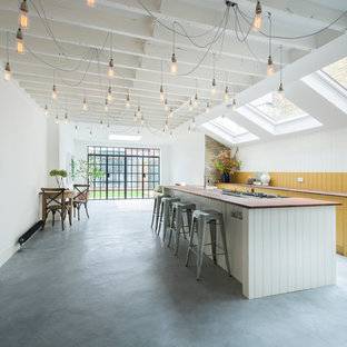 Photo of a large rural galley open plan kitchen in London with wood worktops, concrete flooring, an island, flat-panel cabinets and yellow cabinets.