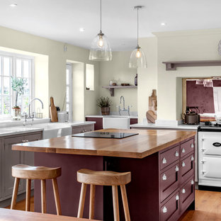 Inspiration for a transitional kitchen in Other with a farmhouse sink, shaker cabinets, beige cabinets, white appliances, medium hardwood floors, with island, brown floor and white benchtop.